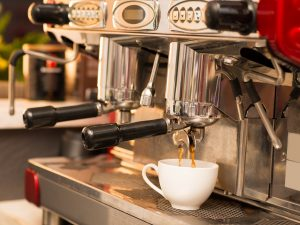 Image of a modern coffee machine making tasty coffee in the coffee shop